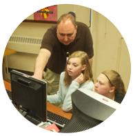 Teacher pointing to a computer with students