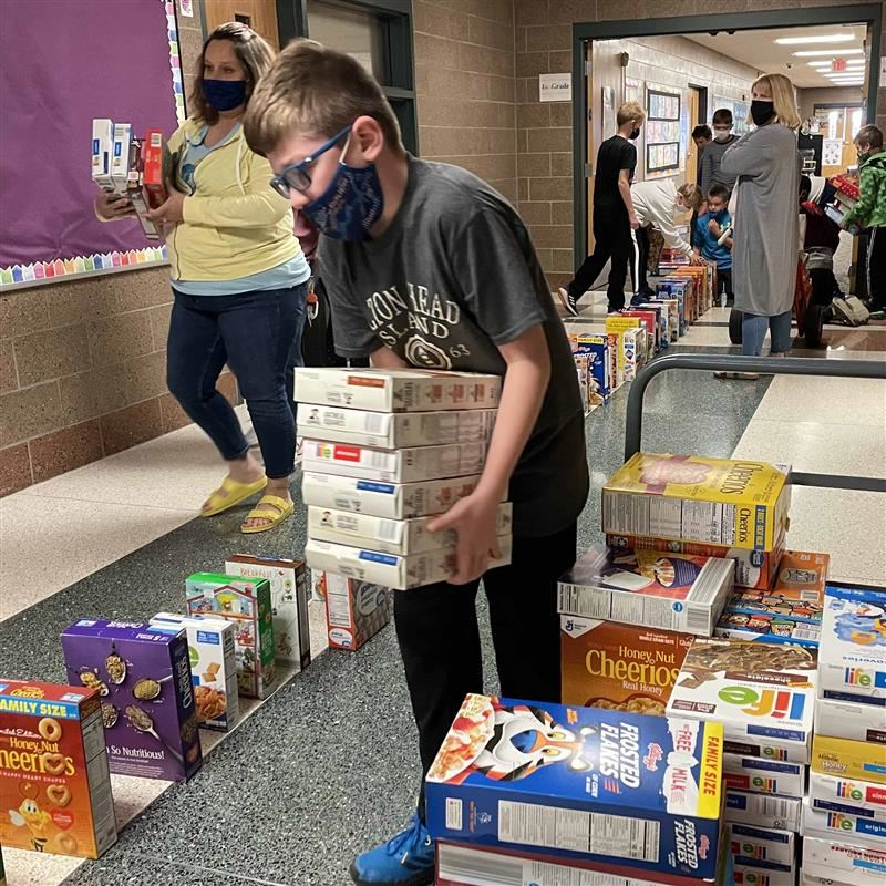 students and teachers make dominoes with cereal boxes
