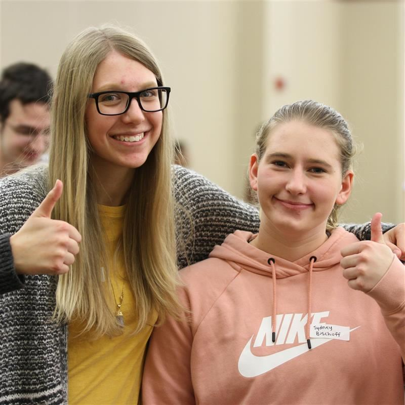two students giving thumbs up
