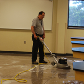 custodian buffs classroom floor with machine