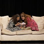 two girls reading book on couch