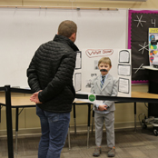 student presenting in front of adult