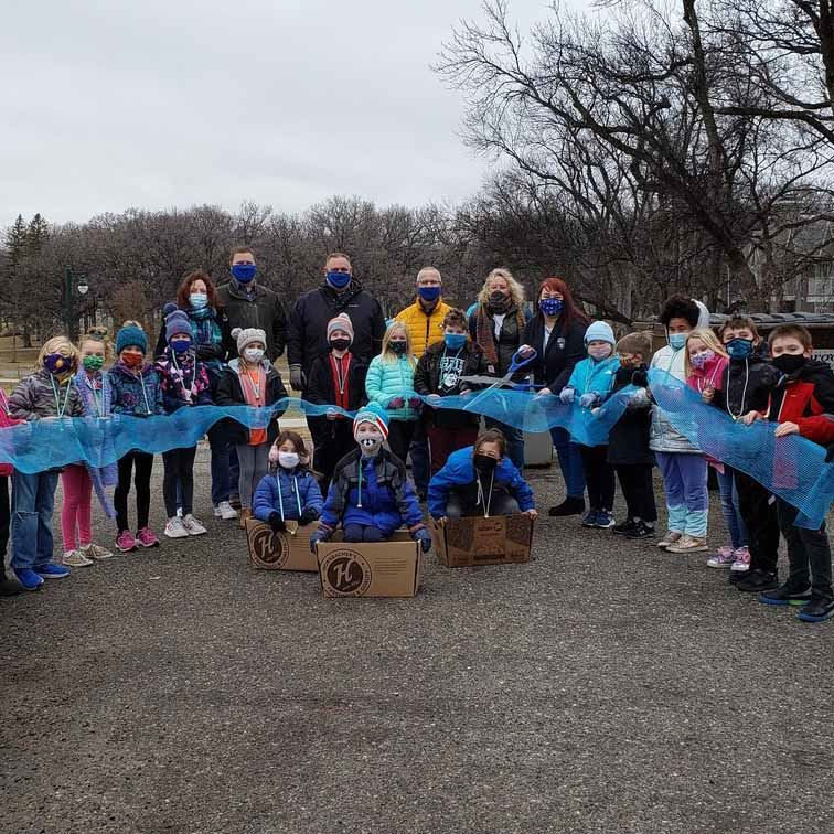 group of students and staff cut blue ribbon