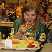 girl eating school lunch from tray in cefeteria